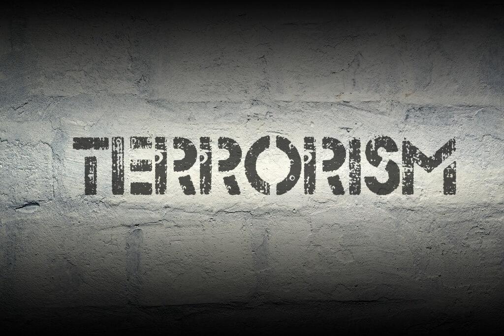 terrorism stencil print on the grunge white brick wall