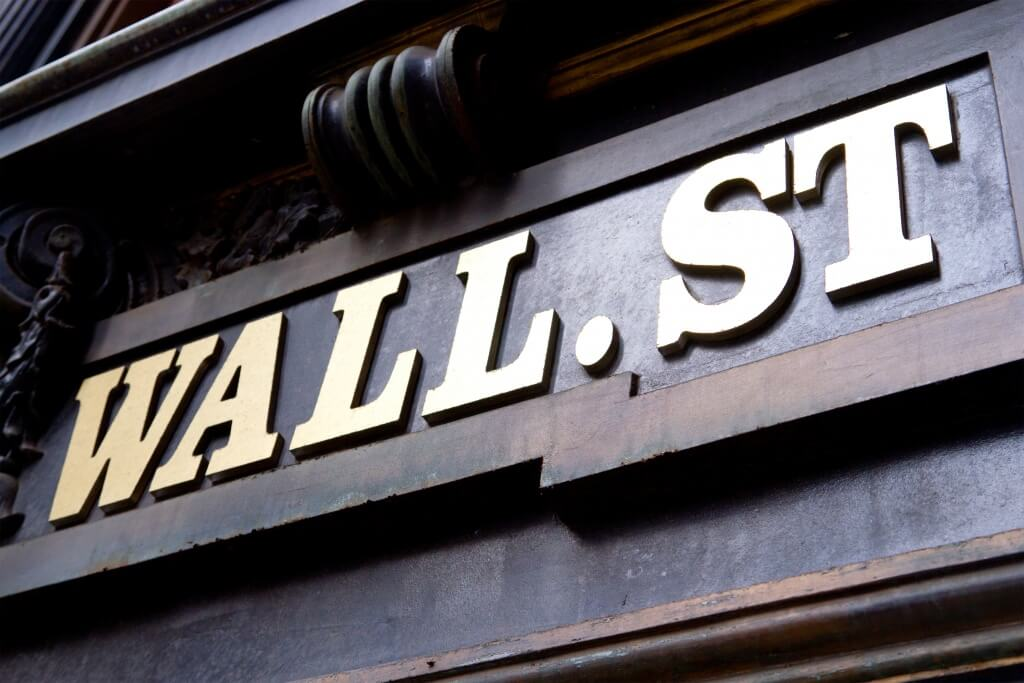 The words Wall Street written on the entrance of a building.